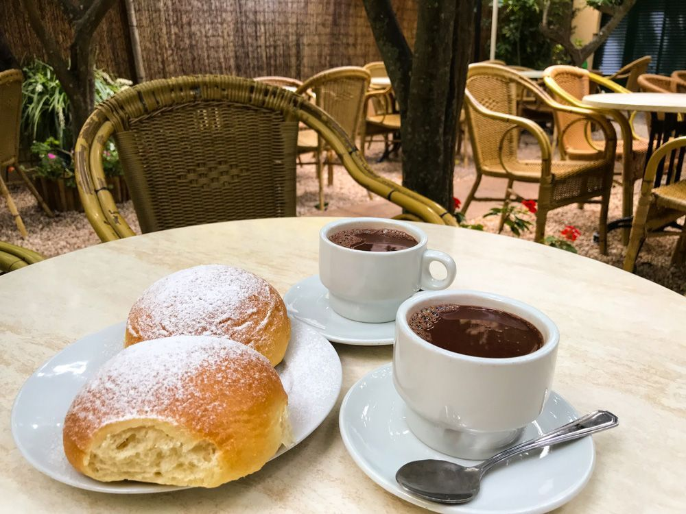 Coca de patata y taza de chocolate, imprescindible si visitas Mallorca