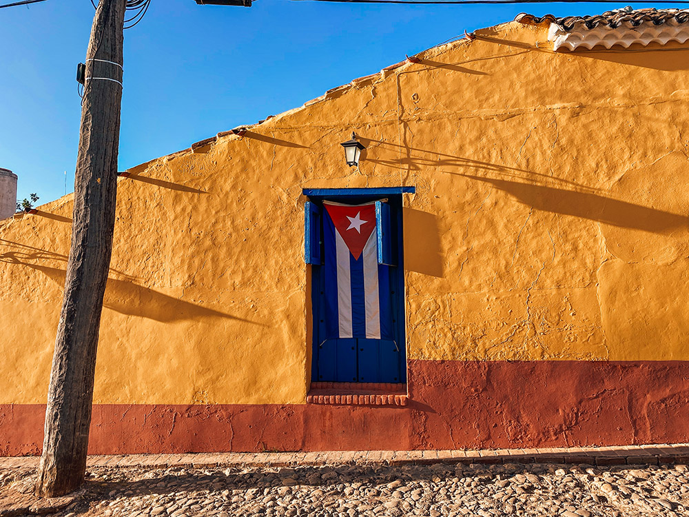 Calle de Trinidad con la bandera de Cuba en una ventana